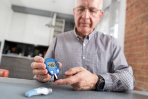 senior man checking blood sugar
